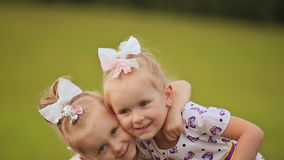 Two little twin sisters are pressed against each other, having fun on a green meadow in summer. Hugging fall on the. Grass stock video