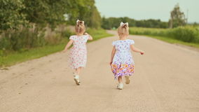 Two little twin sisters run along the road along the forest. Summer sunny day and girls in light dresses. Two little twin sisters run along the road along the stock video footage
