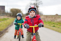 Two little twin toddler boys having fun on bicycles, outdoors. Two little children having fun on bicycles, outdoors. Focus on one boy Stock Photography