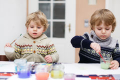 Two little twins boys having fun indoor, painting with different Royalty Free Stock Photos