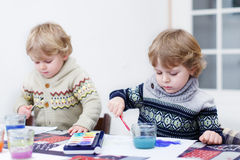Two little twins boys having fun indoor, painting with different Royalty Free Stock Images