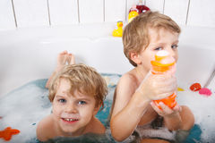 Two little twins boys having fun with water by taking bath in ba Royalty Free Stock Photography