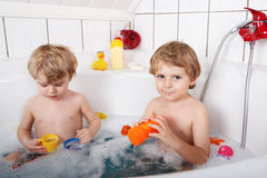 Two little twins boys having fun with water by taking bath in ba Stock Photography