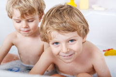 Two little twins boys having fun with water by taking bath in ba Royalty Free Stock Image