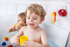 Two little twins boys having fun with water by taking bath in ba Royalty Free Stock Images
