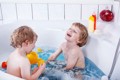 Two little twins boys having fun with water by taking bath in ba Royalty Free Stock Photo