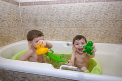 Two little twins children playing together with water by taking bath Royalty Free Stock Photo