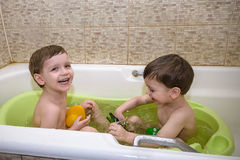 Two little twins children playing together with water by taking bath Stock Images