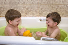Two little twins children playing together with water by taking bath Royalty Free Stock Image