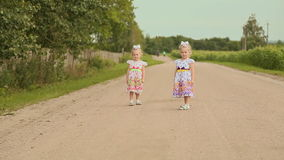 Two little twins sisters in white dresses on the road along the field. Running together. Far Forest. Two little twins sisters in white dresses on the road along stock video footage