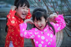 Two little Vietnamese girls play and laugh in national costumes royalty free stock image