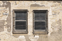 Two little windows with metallic protections. On a stones wall Royalty Free Stock Photography