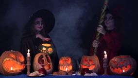Two Little Witches Doing Magic Over Pumpkins At stock footage