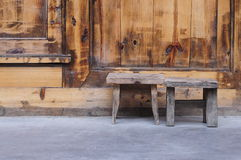 Two little wooden stools. In front the wooden gate Stock Images