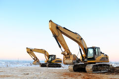 Two loader excavators in winter stock images