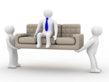 Two loaders bear a sofa with the businessman. Royalty Free Stock Images