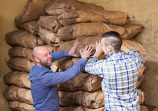 Two loaders handling sacks. Two adult positive loaders handling sacks with something heavy indoors Stock Photos