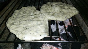 Two Loaf of bread grilled over charcoal. Closeup stock video