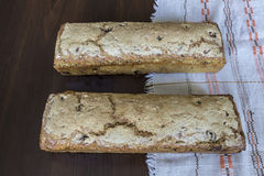 Two loaves of bread baked at home. Polish cuisine. Bread from rye with additives on a linen napkin and on a dark background stock images
