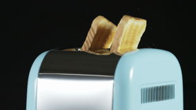 Two Loaves of Bread Jumping Out of an Electric Toaster. Close shot. Black background. Shot on RED Epic stock video
