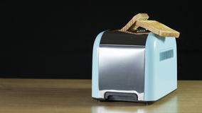 Two Loaves of Bread Jumping Out of an Electric Toaster. Close shot. Black background. Shot on RED Epic stock video footage