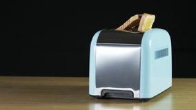 Two Loaves of Bread Jumping Out of an Electric Toaster. Close shot. Black background. Shot on RED Epic stock footage