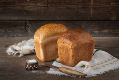 Two loaves of bread, knife, salt lying on a wooden surface Stock Photos
