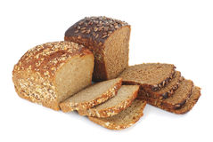 Two loaves of brown bread with cereals. Sliced brown bread. Isolated over white Stock Images
