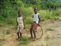 Two local African boys sitting on their simple bicycle wheel and Stock Image