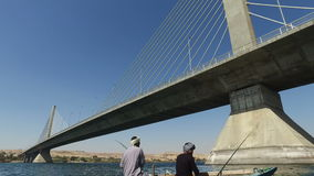 Two local man fishing on Nile under Aswan bridge stock video footage