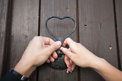 Two locks in the form of hearts in the hands of the newlyweds Royalty Free Stock Image