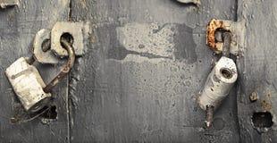 Two locks on an old gray metallic door Stock Photos