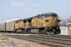 Two locomotives with a freight train. Two old yellow locomotives with a freight train passing through town Stock Photos