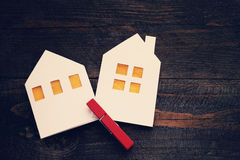 Two lodges from white paper on a wooden background. Symbol of the house, family, cosiness. Stock Photo