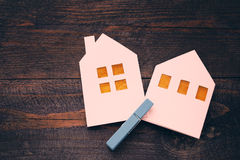 Two lodges from white paper on a wooden background. Symbol of the house, family, cosiness. Stock Photos