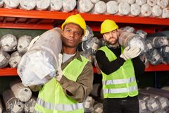 Two logistics workers carry delivery. Two logistics workers of a freight forwarding company in the carpet warehouse transport delivery royalty free stock photo
