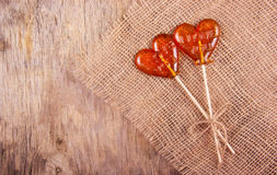 Two lollipop in heart shape on old wooden background. Stock Photo