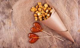 Two lollipop in the shape of a heart and a paper bag of caramel popcorn on wooden background. Royalty Free Stock Photos