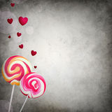 Two lollipops with floating hearts Stock Image