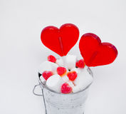 Two Lollipops heart shaped in Small bucket with sweets on white Royalty Free Stock Images