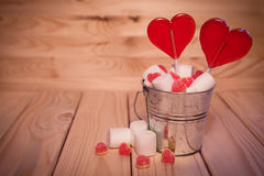 Two Lollipops heart shaped in Small bucket with sweets on wooden stock photos