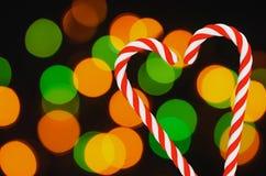 Two lollipops shape of heart on bokeh background. Traditional seasonal treat Stock Photography
