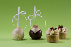 Two lollypops and two muffins Stock Images