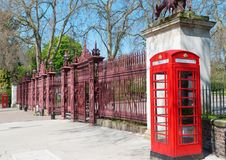 Two London bright red phone cabins infront big door Royalty Free Stock Photo