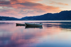 Two lonely boats on calm water of fjord. Stock Image