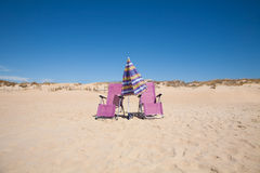 Two lonely chairs and umbrella at beach Royalty Free Stock Photos