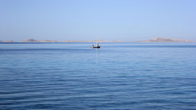 Two lonely fishermen on the sea Royalty Free Stock Images