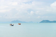 Two lonely fishing boats in a idyllic peacful sea bay. Two lonely fishing boats in a idyllic peacefull sea bay with many islands on background Stock Photos
