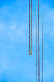 Two long chains with hooks next to four cables on sky Stock Photography