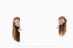 Two long hair women behind a blank sign Stock Photography